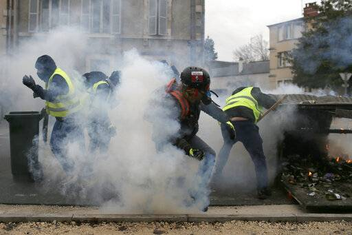 French police fires tear gas as yellow vest demonstrators set up barricades in Bourges, central France, Saturday, Jan. 12, 2019. Paris brought in armored vehicles and the central French city of Bourges shuttered shops to brace for new yellow vest protests. The movement is seeking new arenas and new momentum for its weekly demonstrations. Authorities deployed 80,000 security forces nationwide for a ninth straight weekend of anti-government protests.