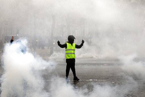 A yellow vest protester taunts riot police during clashes around the Arc of Triomphe in Paris, France, Saturday, Jan. 12, 2019. Authorities deployed 80,000 security forces nationwide for a ninth straight weekend of anti-government protests.