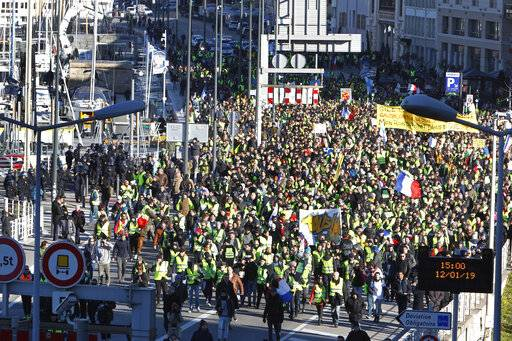 Yellow vest protesters pass through the old harbor as they demonstrate in Marseille, southern France, Saturday, Jan. 12, 2019. Paris brought in armored vehicles and the central French city of Bourges shuttered shops to brace for new yellow vest protests. The movement is seeking new arenas and new momentum for its weekly demonstrations. Authorities deployed 80,000 security forces nationwide for a ninth straight weekend of anti-government protests.