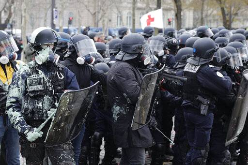 Riot police take position during clashes yellow vest protesters clash around the Arc of Triomphe in Paris, France, Saturday, Jan. 12, 2019. Authorities deployed 80,000 security forces nationwide for a ninth straight weekend of anti-government protests.