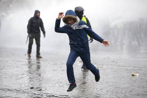 A demonstrator runs away after being sprayed with a water canon in clouds of teargas as yellow vest protesters clash with riot police on the famed Champs Elysees avenue in Paris, France, Saturday, Jan. 12, 2019. Authorities deployed 80,000 security forces nationwide for a ninth straight weekend of anti-government protests.