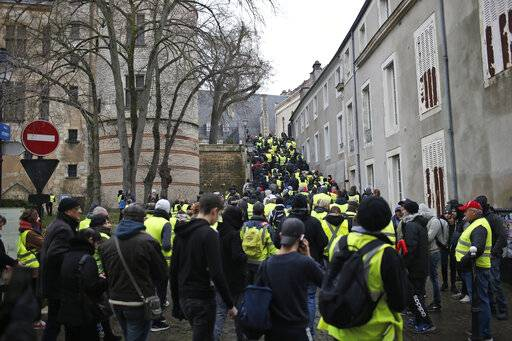 Yellow vest protesters demonstrate in Bourges, central France, Saturday, Jan. 12, 2019. Paris brought in armored vehicles and the central French city of Bourges shuttered shops to brace for new yellow vest protests. The movement is seeking new arenas and new momentum for its weekly demonstrations. Authorities deployed 80,000 security forces nationwide for a ninth straight weekend of anti-government protests.