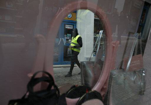 A yellow vest protestor passes a shop window in Bourges, central France, Saturday, Jan. 12, 2019. Paris brought in armored vehicles and the central French city of Bourges shuttered shops to brace for new yellow vest protests. The movement is seeking new arenas and new momentum for its weekly demonstrations. Authorities deployed 80,000 security forces nationwide for a ninth straight weekend of anti-government protests.