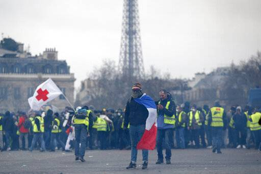 Yellow vest protesters stand near the Arc de Triomphe within view of the Eiffel Tower, background, during a demonstration in Paris, France, Saturday, Jan. 12, 2019. Authorities deployed 80,000 security forces nationwide for a ninth straight weekend of anti-government protests.