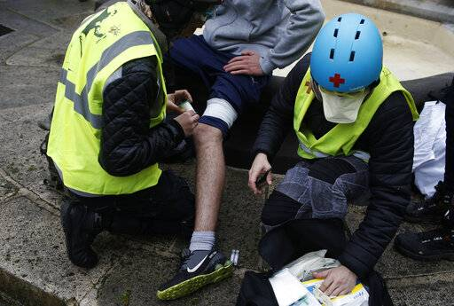 A protester hit by a flash-ball is treated during a yellow vest demonstration in Bourges, central France, Saturday, Jan. 12, 2019. Paris brought in armored vehicles and the central French city of Bourges shuttered shops to brace for new yellow vest protests. The movement is seeking new arenas and new momentum for its weekly demonstrations. Authorities deployed 80,000 security forces nationwide for a ninth straight weekend of anti-government protests.