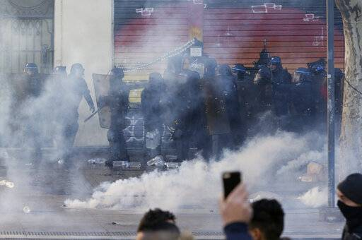 French riot police advances in a cloud of tear gas during a demonstration in Marseille, southern France, Saturday, Jan. 12, 2019. Paris brought in armored vehicles and the central French city of Bourges shuttered shops to brace for new yellow vest protests. The movement is seeking new arenas and new momentum for its weekly demonstrations. Authorities deployed 80,000 security forces nationwide for a ninth straight weekend of anti-government protests.