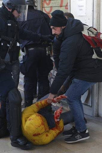 French plainclothes detain a bleeding, handcuffed protestor, during a yellow vest demonstration in Marseille, France, Saturday, Jan. 12, 2019. Paris brought in armored vehicles and the central French city of Bourges shuttered shops to brace for new yellow vest protests. The movement is seeking new arenas and new momentum for its weekly demonstrations. Authorities deployed 80,000 security forces nationwide for a ninth straight weekend of anti-government protests.