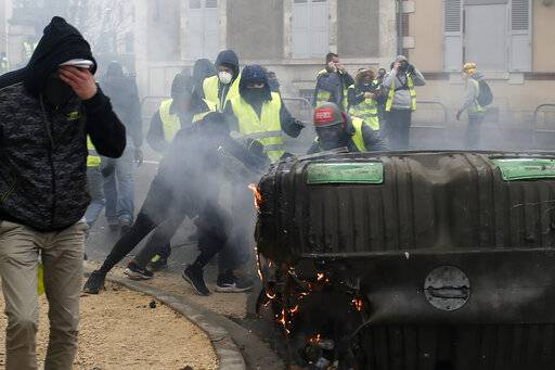 A man rubs his eyes as others set up barricades in a cloud of tear gas during demonstration in Bourges, central France, Saturday, Jan. 12, 2019. Paris brought in armored vehicles and the central French city of Bourges shuttered shops to brace for new yellow vest protests. The movement is seeking new arenas and new momentum for its weekly demonstrations. Authorities deployed 80,000 security forces nationwide for a ninth straight weekend of anti-government protests.
