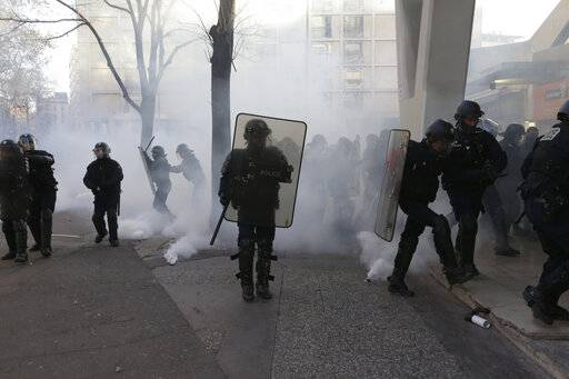 French police take positions in a cloud of tear gas during a yellow vest protest in Marseille, southern France, Saturday, Jan. 12, 2019. Paris brought in armored vehicles and the central French city of Bourges shuttered shops to brace for new yellow vest protests. The movement is seeking new arenas and new momentum for its weekly demonstrations. Authorities deployed 80,000 security forces nationwide for a ninth straight weekend of anti-government protests.