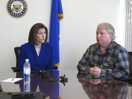 David Pritchett, a furloughed worker for the U.S. Bureau of Land Management, looks on as Sen. Catherine Cortez Masto, D-Nev., talks to reporters Friday, Jan. 11, 2019, in her office in Reno about the impacts of the partial government shutdown. Pritchett, a BLM planner in Reno, says the effects of the shutdown will have a ripple effect on federal land management long after the government fully reopens because of deadlines that were missed for federal permits on a whole range of projects, from gold mines to large recreational events.