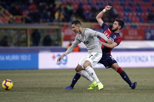 Juventus' Cristiano Ronaldo, left, challenges for the ball with Bologna's Arturo Calabresi during a round of 16 Italian Cup soccer match between Bologna and Juventus at the Renato Dall'Ara stadium in Bologna, Italy, Saturday, Jan. 12, 2019.