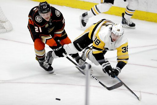 Anaheim Ducks defenseman Jake Dotchin, left, vies for the puck with Pittsburgh Penguins center Derek Grant during the second period of an NHL hockey game in Anaheim, Calif., Friday, Jan. 11, 2019.