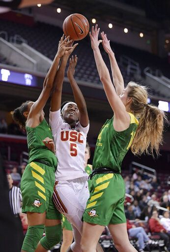 Southern California's Ja'Tavia Tapley, center, shoots as Oregon's Satou Sabally, left, and Lydia Giomi defend during the second half of an NCAA college basketball game Friday, Jan. 11, 2019, in Los Angeles. Oregon won 93-53.