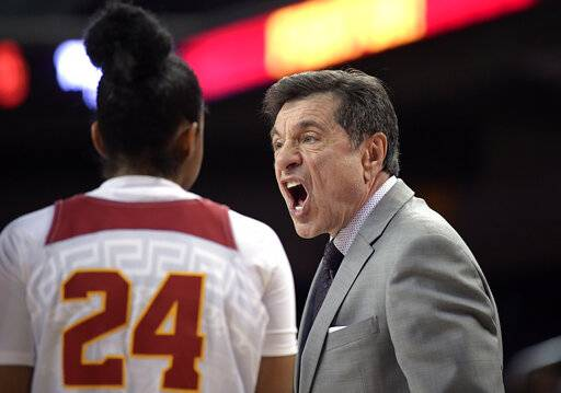 Southern California coach Mark Trakh, right, talks with his players, including Desiree Caldwell, during the first half of the team's NCAA college basketball game against Oregon on Friday, Jan. 11, 2019, in Los Angeles.