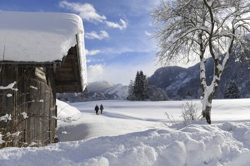 Two woman make their way through the fresh snow in Lofer, Austrian province of Salzburg on Friday, Jan. 11, 2019.