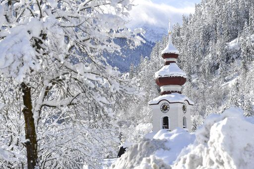 The steeple of the Loferer church is seen through the snow on Friday, Jan. 11, 2019 in Lofer, Austrian province of Salzburg.