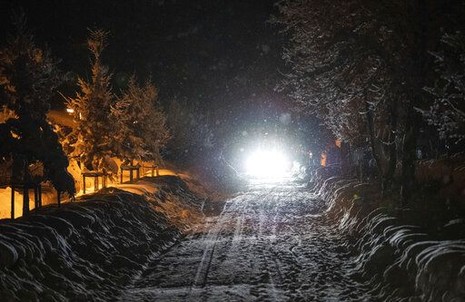 A car drives on a snow covered street at the Bavarian city Berchtesgaden, Germany, Friday, Jan 11, 2018, after Austria and southern Germany were hit by heavy snowfall. (Lino Mirgeler/dpa via AP)