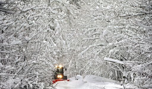 A road in a forest is cleaned from snow in Schongau, southern Germany, Thursday, Jan. 10, 2019 after Austria and southern Germany were hit by heavy snowfall. (Karl-Josef Hildenbrand/dpa via AP)