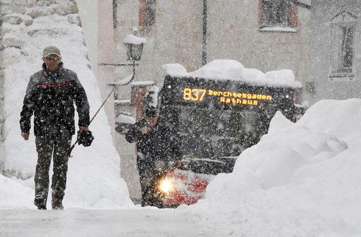 A man and a bus make their way on a street in Berchtesgaden, southern Germany, Thursday, Jan. 10, 2019 after large parts of southern Germany and Austria were hit by heavy snowfall. (Tobias Hase/dpa via AP)