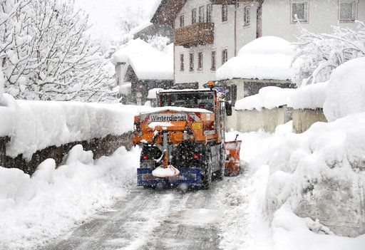 A snow plough cleans a street in Berchtesgaden, southern Germany, Thursday, Jan. 10, 2019 after large parts of southern Germany and Austria were hit by heavy snowfall. (Tobias Hase/dpa via AP)