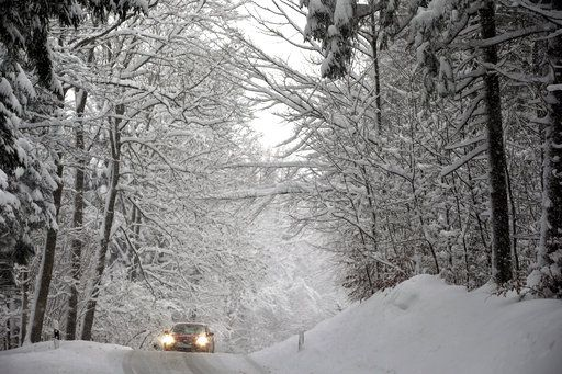A car drives on a road through a forest in Schongau, southern Germany, Thursday, Jan. 10, 2019 after Austria and southern Germany were hit by heavy snowfall. (Karl-Josef Hildenbrand/dpa via AP)