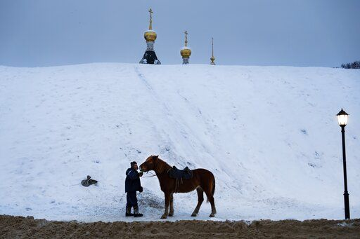 A man prepares a horse to ride tourists during a cold winter day at a hill, near the Assumption Cathedral built in XVI century in the background, in the small Russian town of Dmitrov, about 75 kilometers (47 miles) north from Moscow, Russia, Saturday, Jan. 12, 2019. Temperatures dipped to -10 C (14 F) in Moscow and -13 C (9 F) at night.