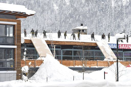 Solidiers from the Austrian Bundesheer clean a roof from snow on Saturday, Jan. 12, 2019 in Waidring. Austrian province of Tyrol.