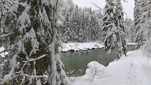 Kayaker make their way on the river Saalach on Saturday, Jan. 12, 2019 in Lofer, Austrian province of Salzburg.