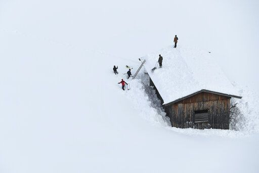 Men clean a roof from snow  in Lofer, Austrian province of Salzburg on Friday, Jan. 11, 2019.