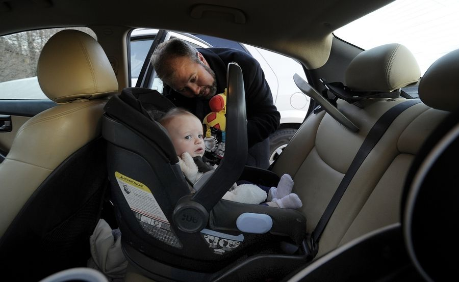 Daily Herald Digital Editor Travis Siebrass positions his 11-month-old daughter into her rear-facing car seat. A new law requires children up to age 2 to be placed in rear-facing child seats.
