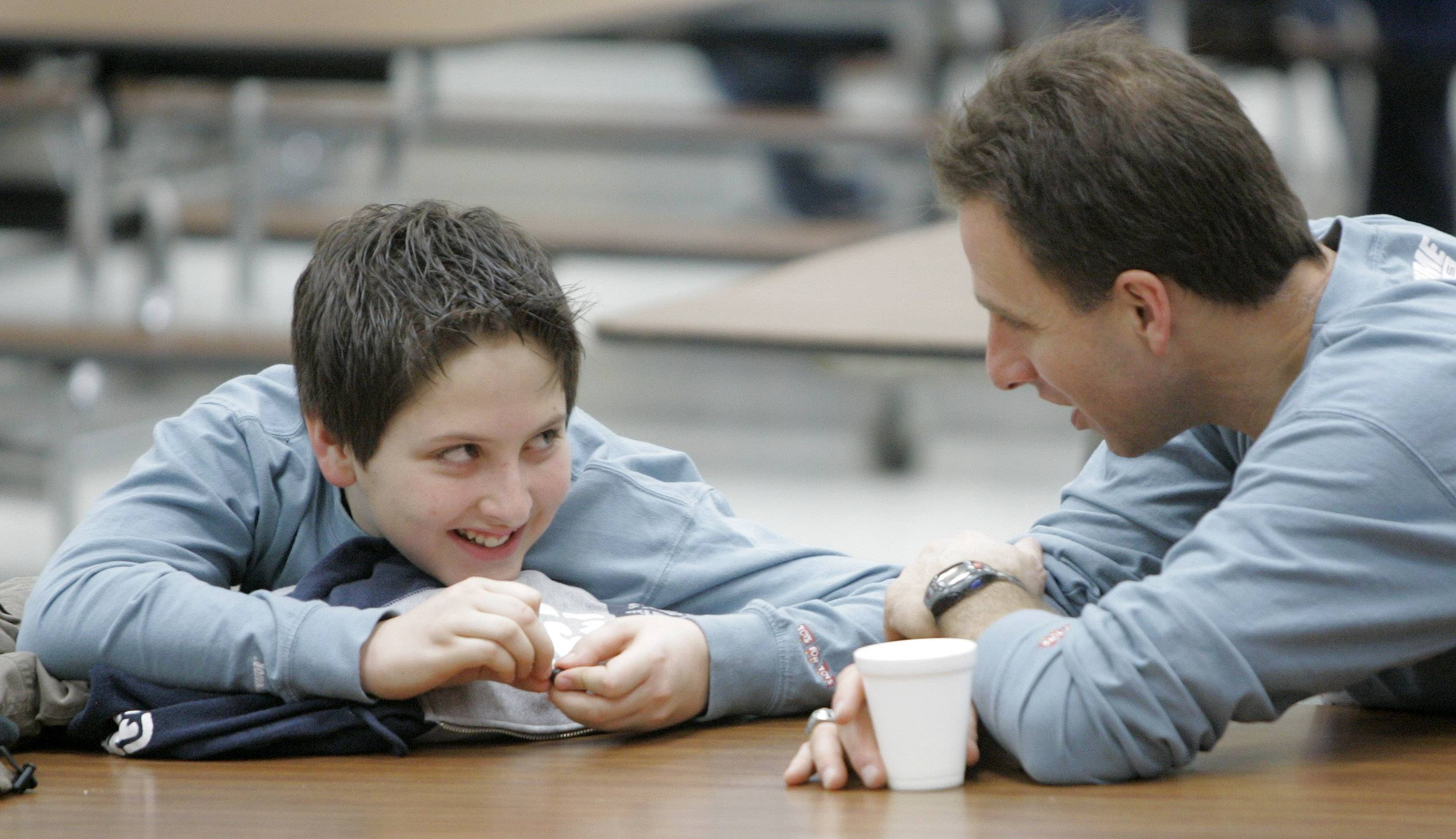 Naperville North High School health teacher and diving coach Steven Mazzarella, right, shares a moment at a dad's breakfast with his son, Matthew, then 12, at Madison Junior High School in Naperville.