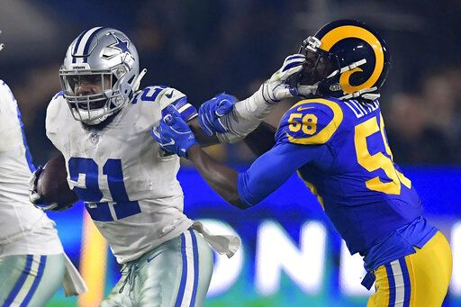 Dallas Cowboys running back Ezekiel Elliott pushes off Los Angeles Rams inside linebacker Cory Littleton during the first half in an NFL divisional football playoff game Saturday, Jan. 12, 2019, in Los Angeles.