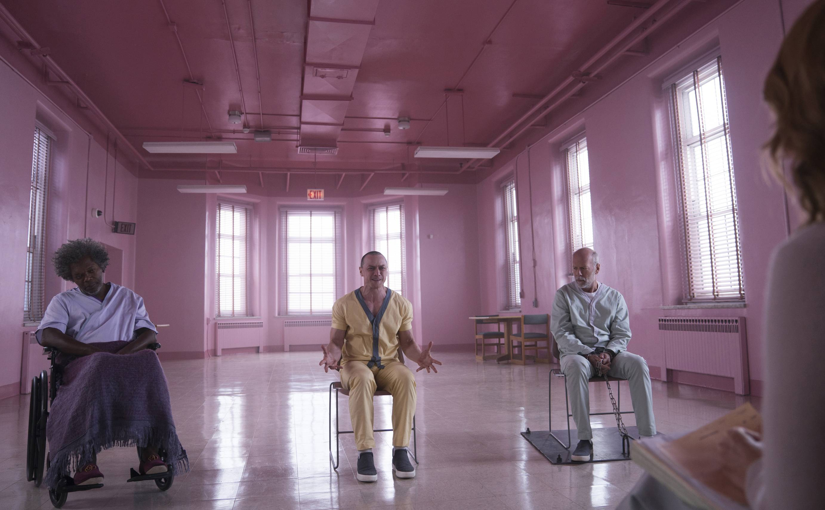 "In a hospital room painted pink, three men professing super powers (Samuel L. Jackson, left, James McAvoy and Bruce Willis) get interrogated during M. Night Shyamalan's ""Glass."""