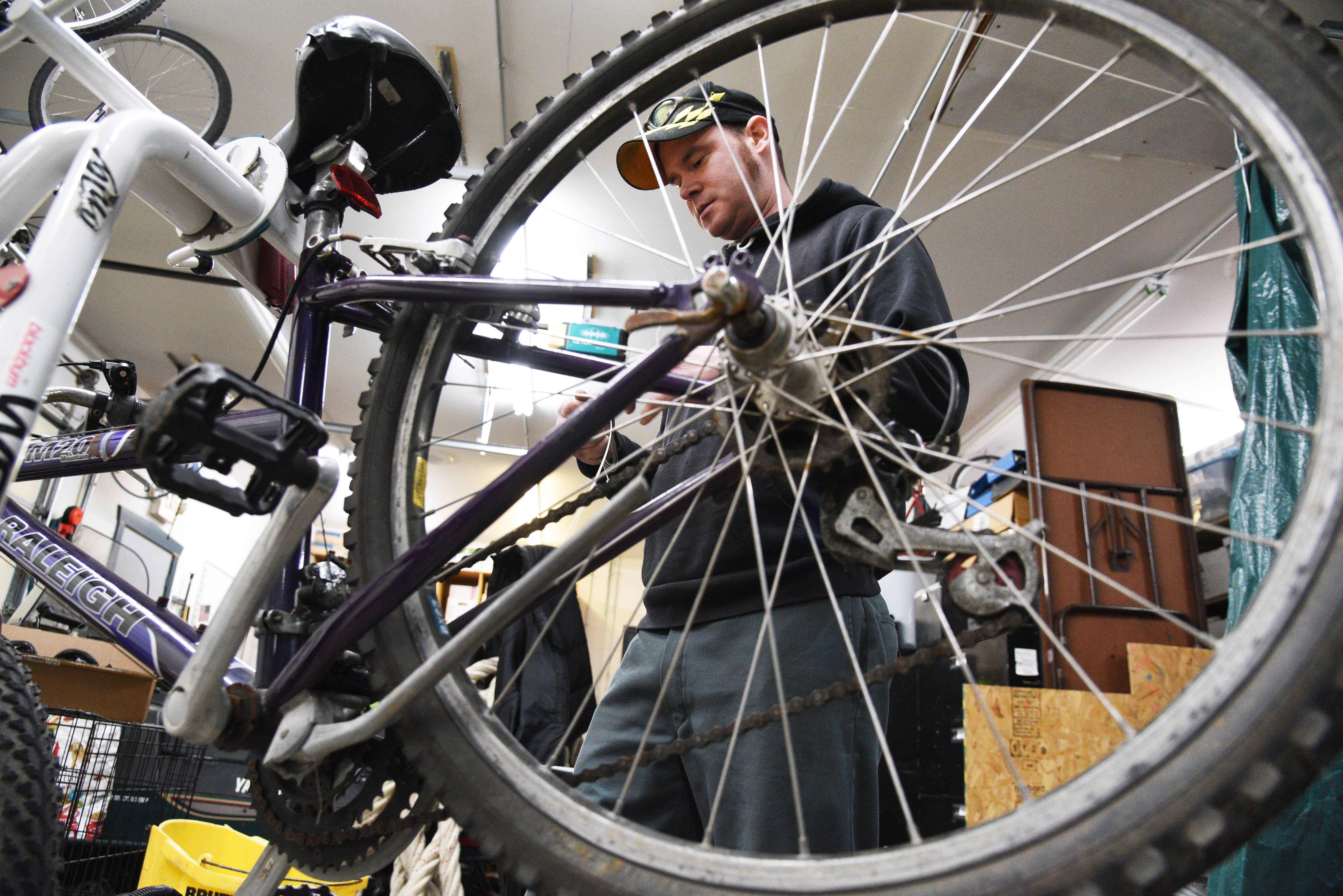 Patrick Tracy of Round Lake spends part of his off day Wednesday fixing bikes at the Round Lake Park Police Department. They'll be donated to people in need in the community.