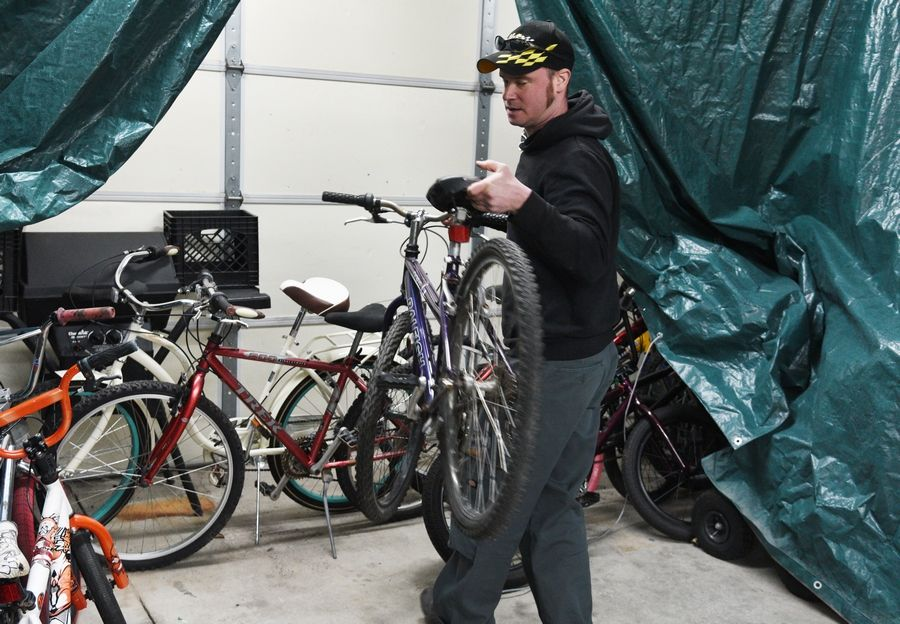 Patrick Tracy of Round Lake grabs a bike needing work at the Round Lake Park Police Department. Tracy completes minor repairs for the new program to repurpose abandoned bikes.