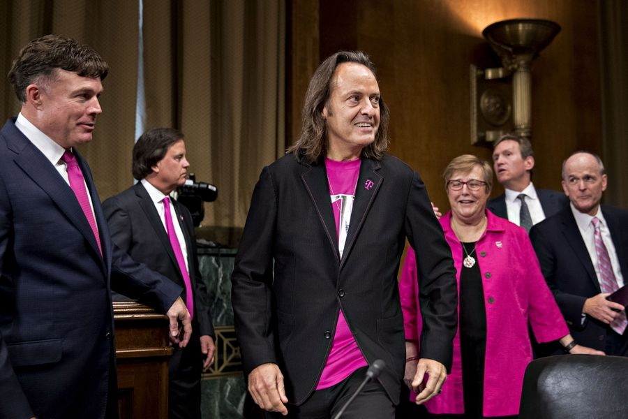 John Legere, chief executive officer of T-Mobile US Inc. (center) arrives at a Senate hearing in Washington, D.C., on June 27, 2018.
