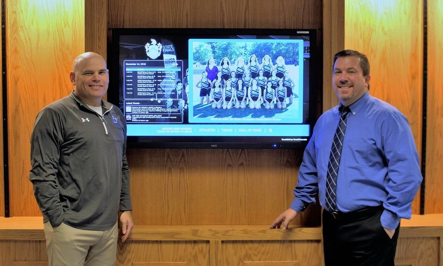 Athletic director Dave Carli, right, and assistant athletic director Matt Hahn unveil the interactive, touchscreen monitor in the Geneva High School Contest Gym Foyer.