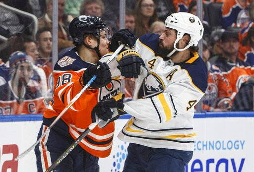 Buffalo Sabres' Zach Bogosian (4) and Edmonton Oilers' Jesse Puljujarvi (98) rough it up during second period NHL hockey action in Edmonton, Alberta, on Monday, Jan. 14, 2019. (Jason Franson/The Canadian Press via AP)