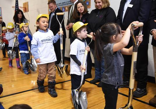Students hand ceremonial shovels to Wheaton Warrenville Unit District 200 school board members Tuesday as they prepare to break ground on a new Jefferson Early Childhood Center in Wheaton.