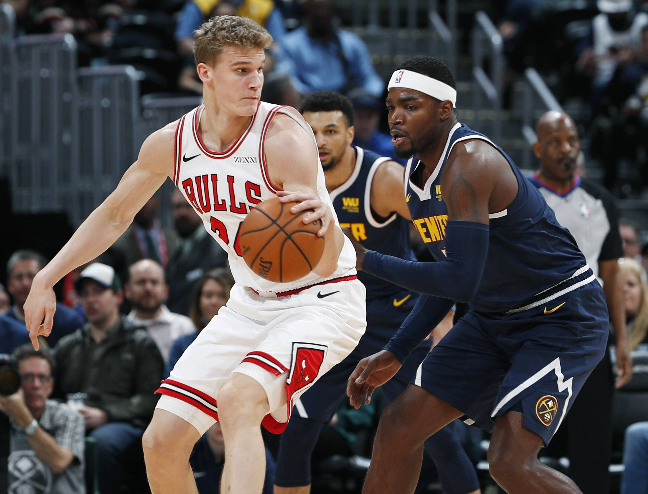 Chicago Bulls forward Lauri Markkanen, left, pulls in a loose ball as Denver Nuggets forward Paul Millsap defends in the first half of an NBA basketball game, Thursday, Jan. 17, 2019, in Denver.