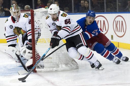 Chicago Blackhawks defenseman Erik Gustafsson (56) works with the puck as New York Rangers right wing Jesper Fast (17) reaches for it during the second period of an NHL hockey game Thursday, Jan. 17, 2019, at Madison Square Garden in New York.