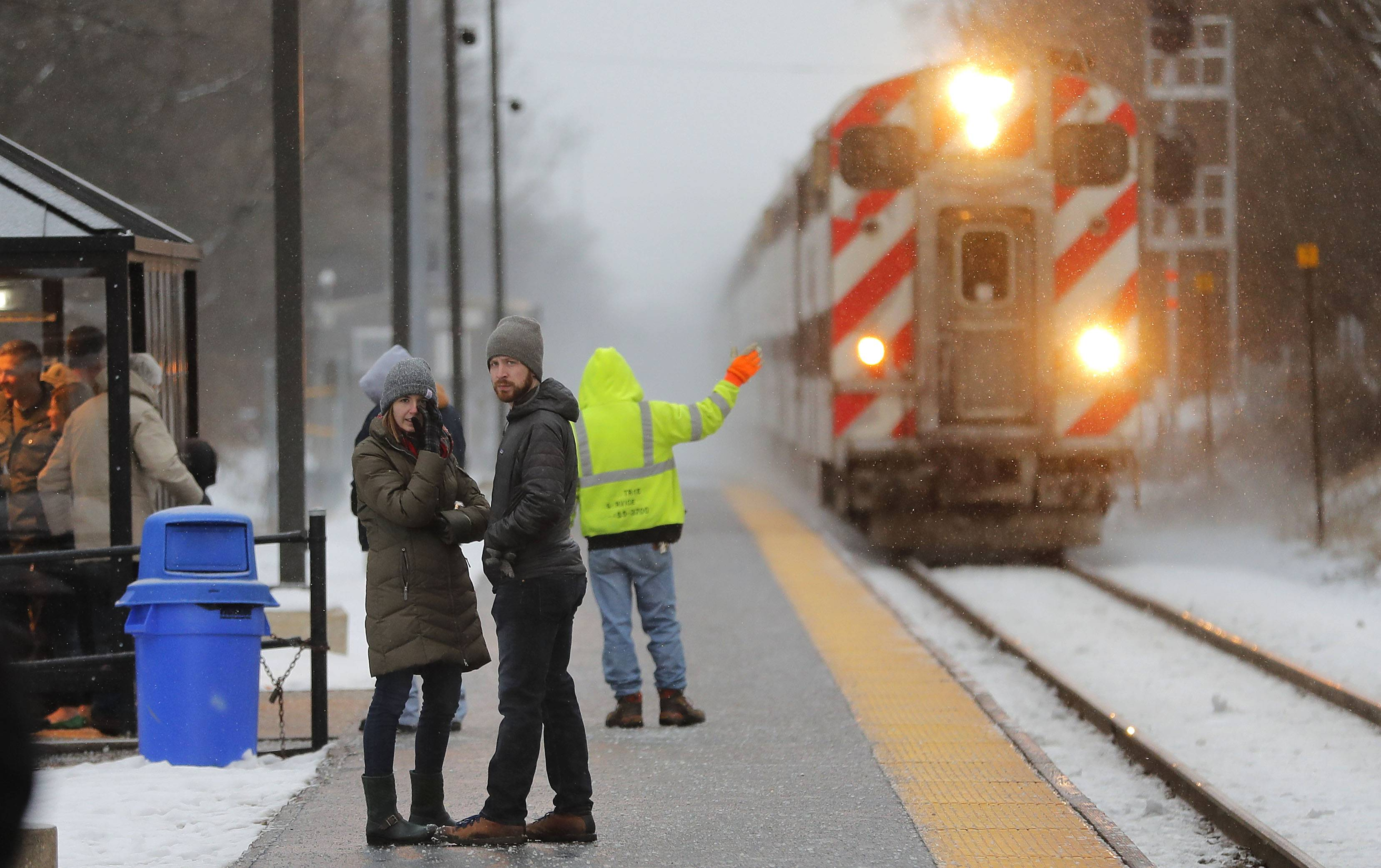 Metra commuters wait for a train as snow begins to fall Friday in Libertyville.