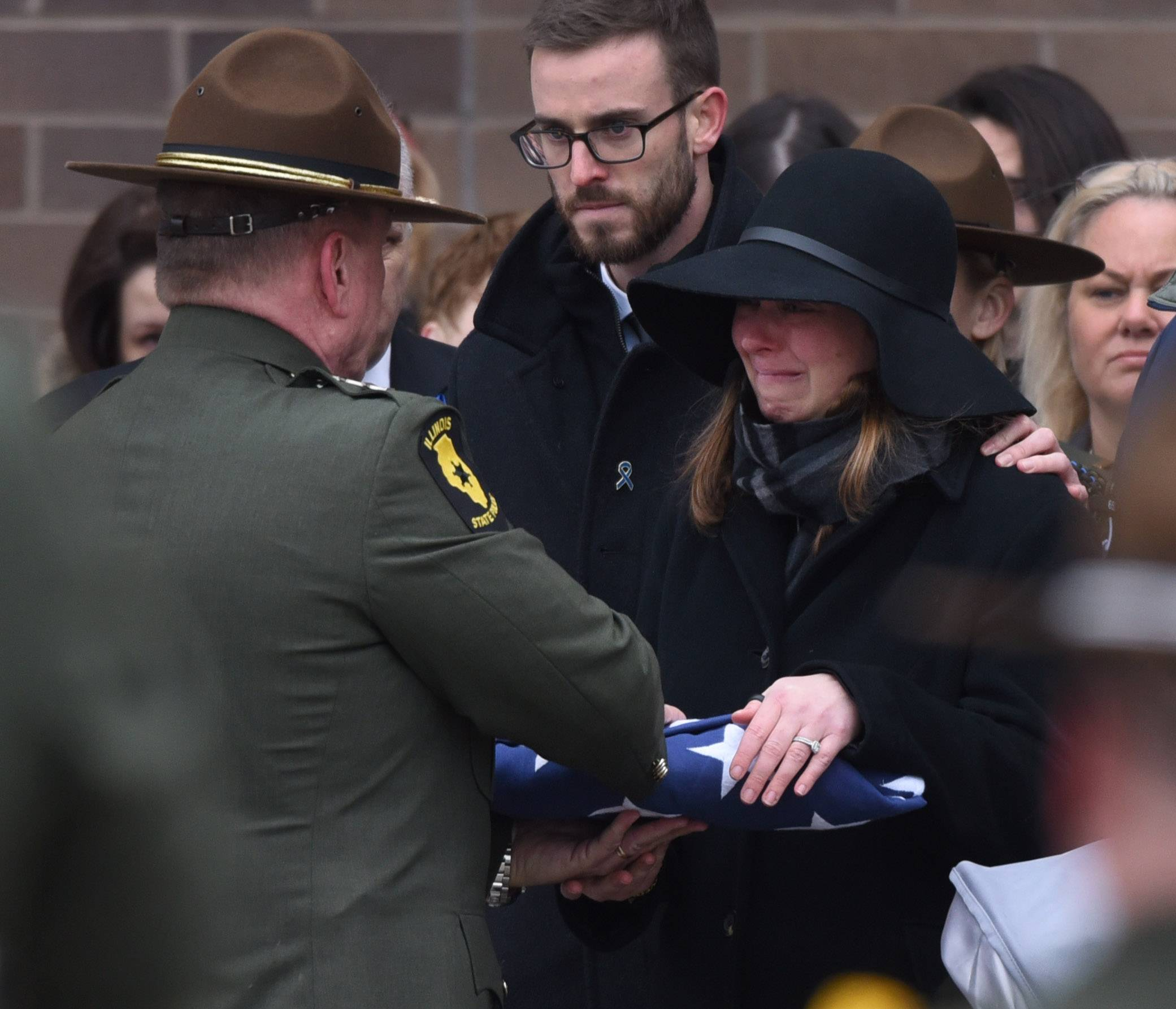 Illinois State Police Director Leo P. Schmitz hands the folded U.S. Flag to Halley Lambert during the funeral for her husband, Illinois State Police Trooper Christopher Lambert, at Willow Creek Community Church in South Barrington Friday.
