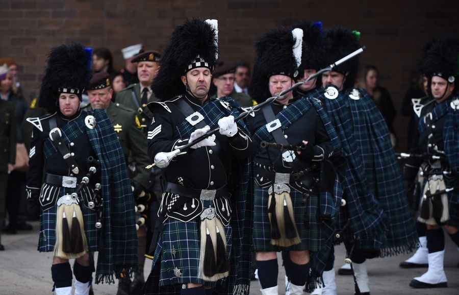 Bagpipers from the Chicago police Bagpipes and Drums of the Emerald Society and the Illinois State Police exit the church during the funeral for Illinois State Police Trooper Christopher Lambert at Willow Creek Community Church in South Barrington Friday.
