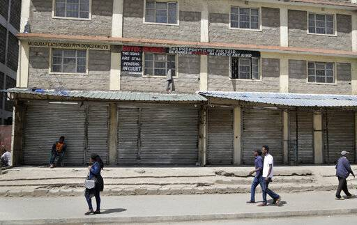 Kenyans walk past closed shops in the Eastleigh area of the capital, after members of the business community there closed the shops as a protest to condemn Tuesday's attack on a hotel complex, in Nairobi, Kenya, Friday, Jan. 18, 2019. Extremists stormed a luxury hotel complex in Kenya's capital on Tuesday, setting off explosions and gunning down people at cafe tables in an attack claimed by militant group al-Shabab.