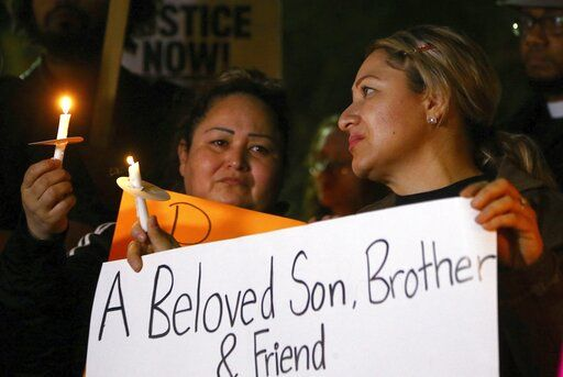 Sandra Gonzalez, left, mother of slain 14-year-old boy shot by Tempe Police, joins another family member, right, and others in front of the Tempe Police headquarters to hold a protest and vigil for the boy shot to death as police say they were pursuing a burglary suspect who they thought had a handgun, Thursday, Jan. 17, 2019, in Tempe, Ariz. It turns out, according to police, the teen had a replica gun.