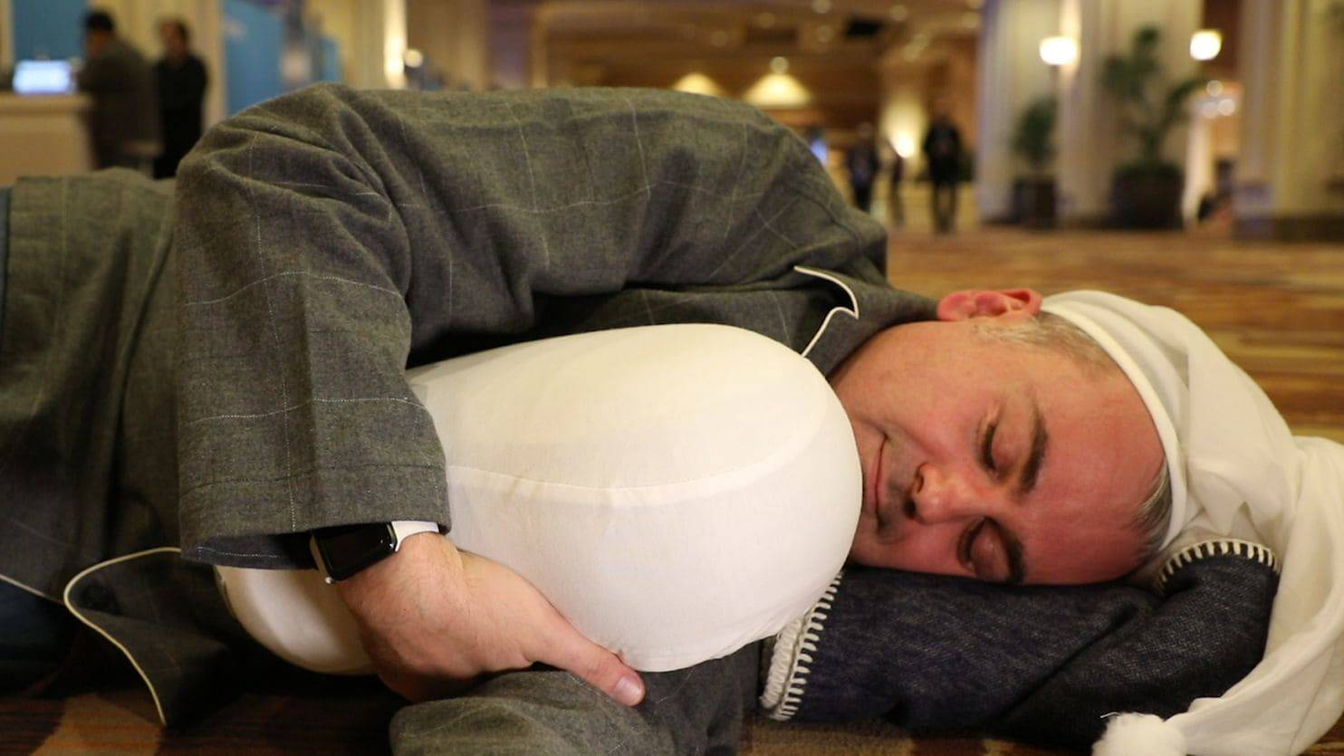 Columnist Geoffrey Fowler tries snuggling with Somnox on the floor of the CES trade show. (Yes, he brought pajamas.)