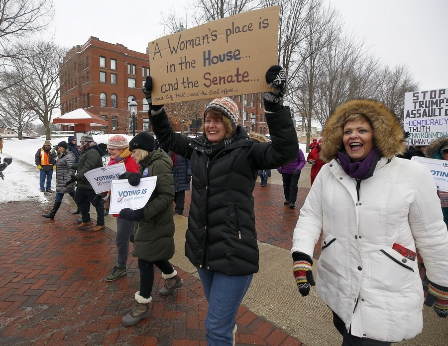 Britta McKenna, center with sign, and Maureen O'Brien, both of Batavia, head down Third Street Saturday during the Fox Valley Women's March in Geneva. The rally started at the Kane County Courthouse and they marched to South Street.