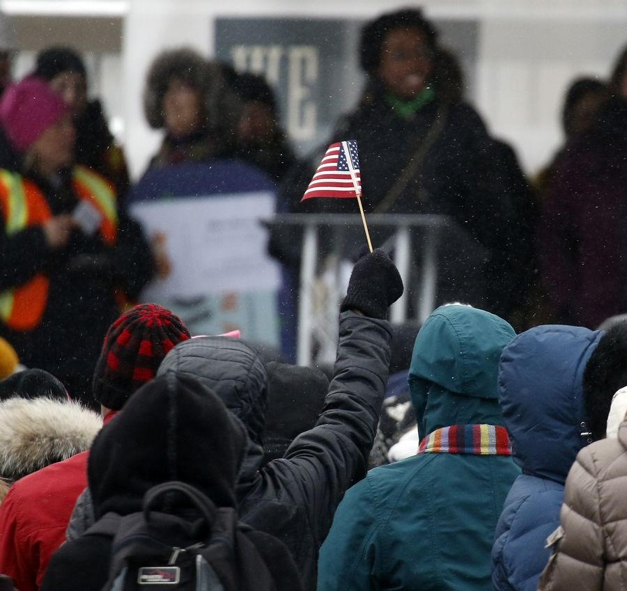 A person holds up a flag as U.S. Rep. Lauren Underwood, a Naperville Democrat, speaks to the crowd Saturday during the Fox Valley Women's March in Geneva.