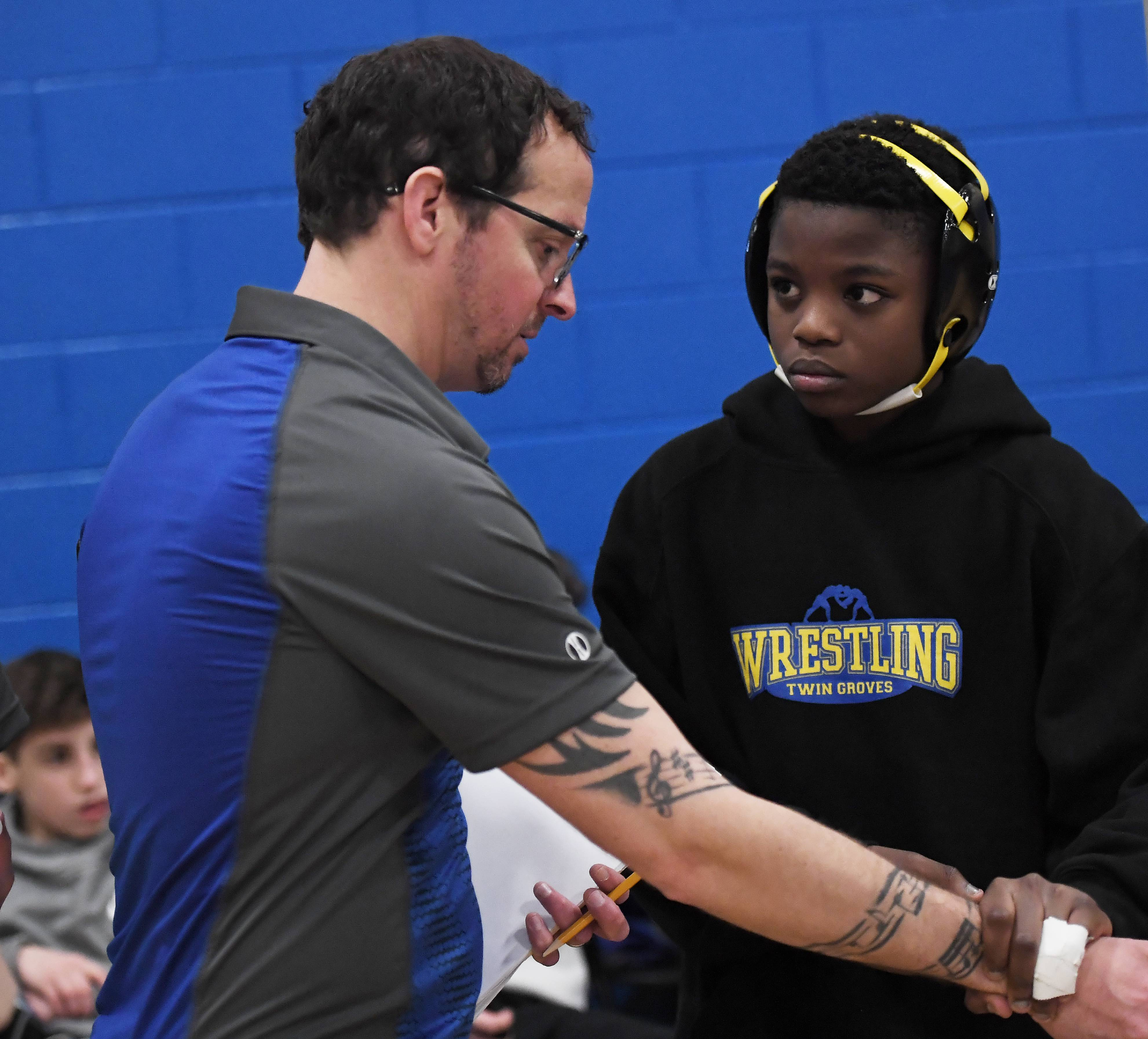Adam Greenberg, Twin Groves Middle School wrestling coach in Buffalo Grove, instructs Themba Sitshela, who was in the 105-pound weight class, with some last-minute techniques at the 6th annual Lindsey Durlacher Wrestling Tournament in Buffalo Grove on Saturday.